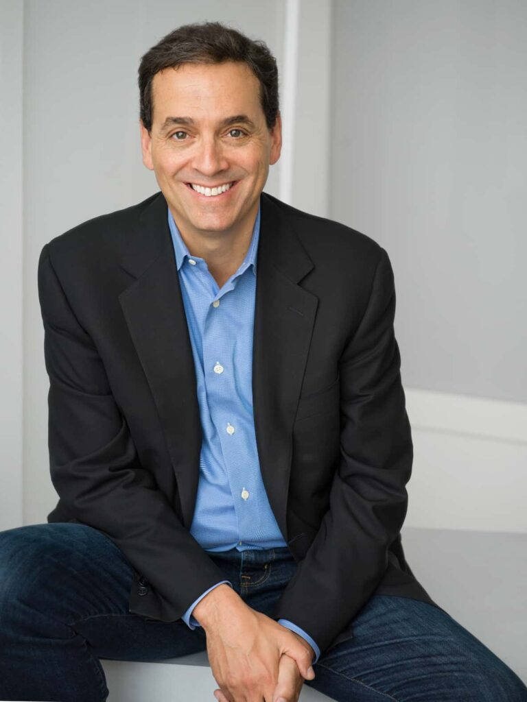 Daniel H. Pink wearing a suit and tie smiling at the camera